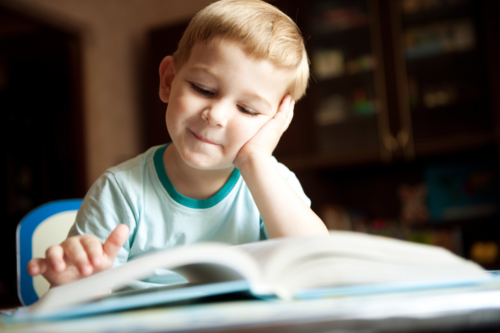 young boy smiling as he reads a book