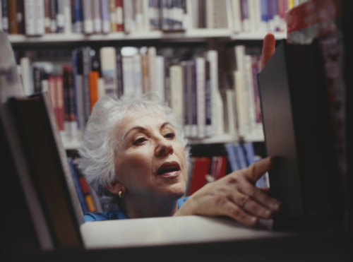 mature woman placing a book on a library shelf