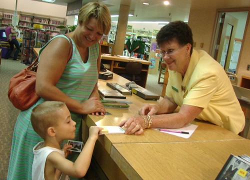 a library staff person helps a small boy at a library service desk