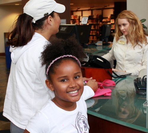 A girls smiles at the camera while standing at a library circulation desk