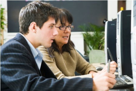 Instructor helping a young man at a computer