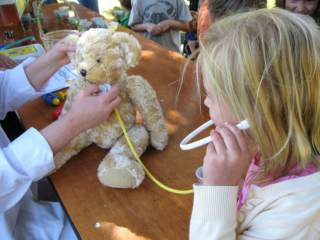 A young assistant helps the doctor listen to a loved bear's heart at the Portola Valley Library Teddy Bear Picnic and Toy Health Check. Image via San Mateo County Library on Flickr