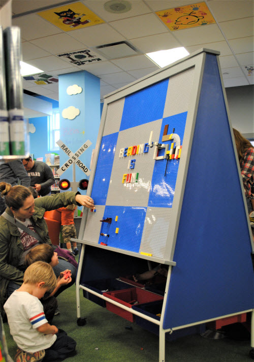 Photo of a large LEGO easel and on the ceiling are tiles painted by library patrons.
