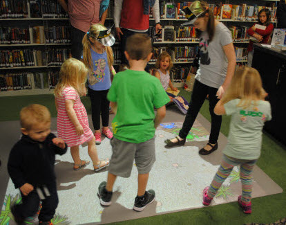 Photo of children playing with the MotionMagix floor projector. Images are projected onto the floor and are interactive.