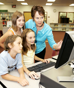 librarian with kids at computer