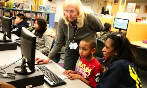 Sandy Sherwood helps six-year-old Kavon Young, with his mom Barbara Poole, with the computer at the Waukegan Public Library Wednesday, February 10, 2010. [Photo by Karen Kring]