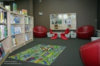 Photo of children's area with chairs, bookshelves and carpet.