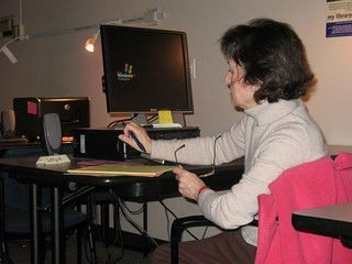 Woman sits at a computer writing some notes