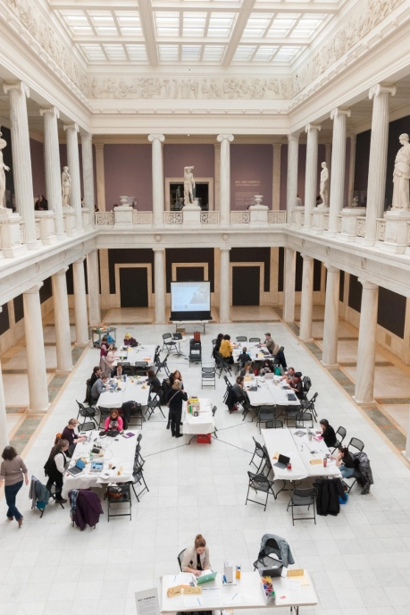 Overhead view of participants sitting at tables for a Wikipedia editing event in the Hall of Sculpture at the Carnegie Museum of Art.